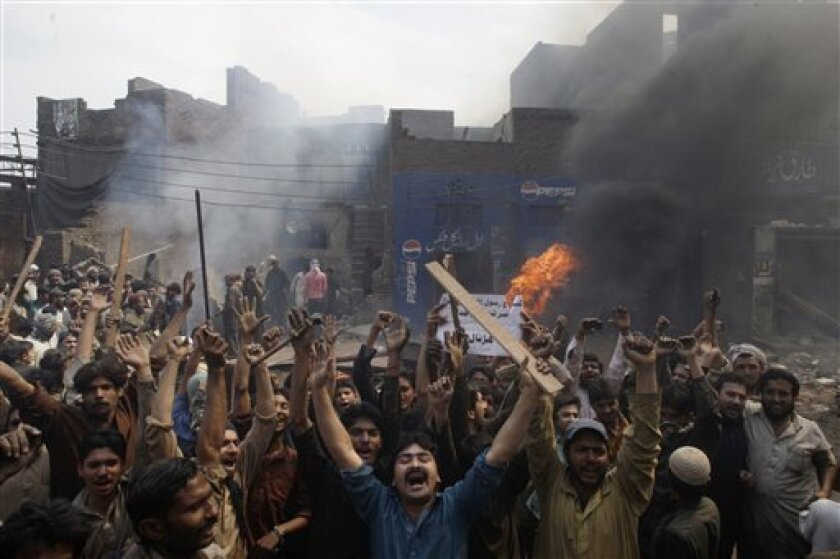 """An angry mob reacts after burning Christian houses in Lahore, Pakistan, Saturday, March 9, 2013. A mob of hundreds of people in the eastern Pakistani city of Lahore attacked a Christian neighborhood Saturday and set fire to homes after hearing accusations that a Christian man had committed blasphemy against Islam's prophet Mohammed, said a police officer. Placard center reads, """" Blasphemer is liable to death."""" (AP Photo/K.M. Chaudary)"""