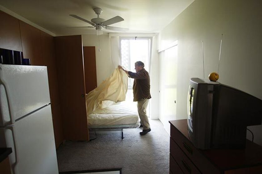 A formerly homeless man makes up his bed in a development in Santa Monica.