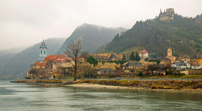 An Austrian town appears out of the fog during a river cruise through the Wachau Valley.