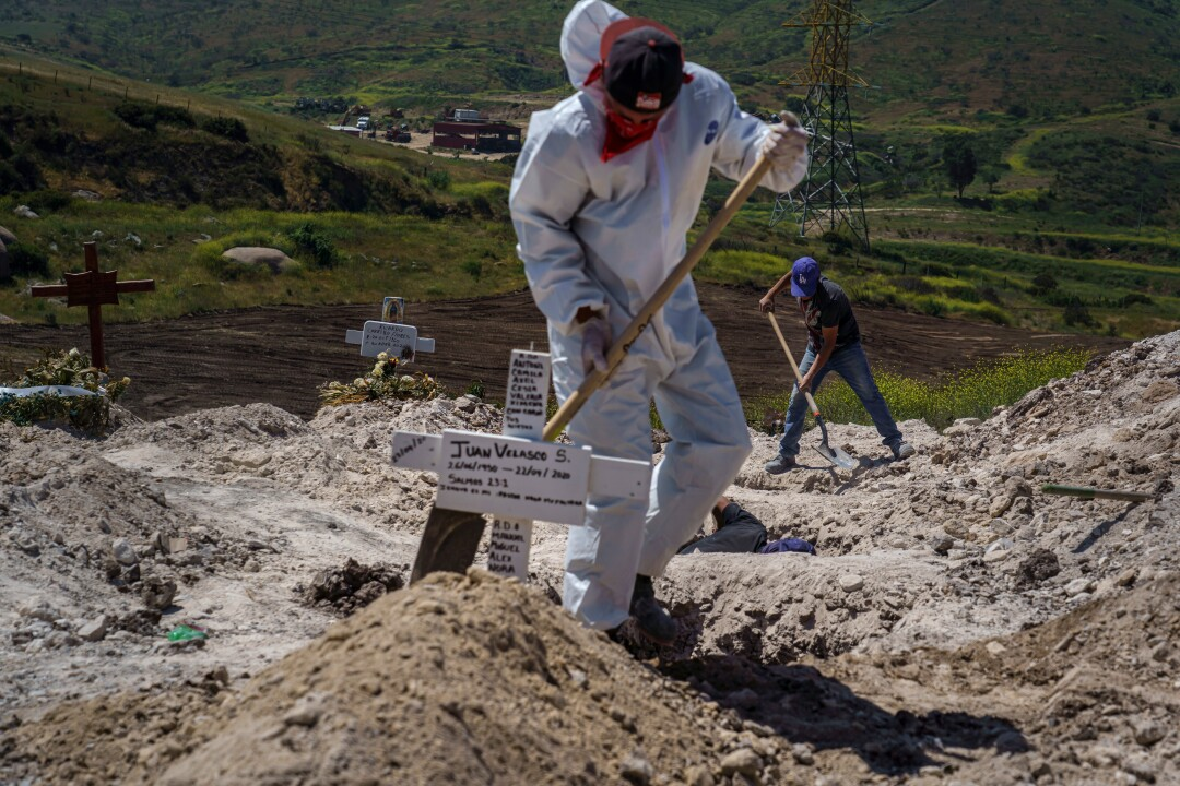 Workers bury Juan Velasco, who died of COVID-19 symptoms, at Tijuana's Municipal Cemetery No. 13.