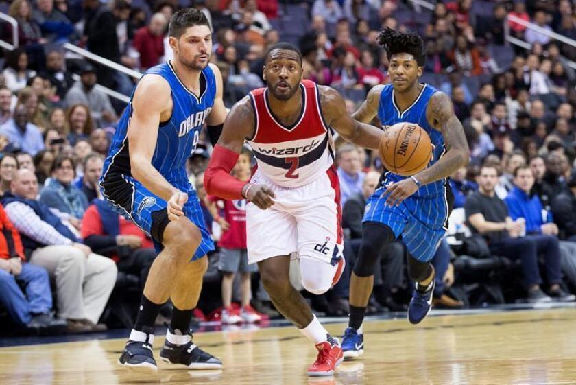 Nikola Vucevic (i) y Elfrid Payton (d) de Magic siguen a John Wall (c) de Wizards, durante un partido entre Magic y Wizards por la NBA en el Verizon Center de Washington (DC, EE.UU.). EFE/Archivo