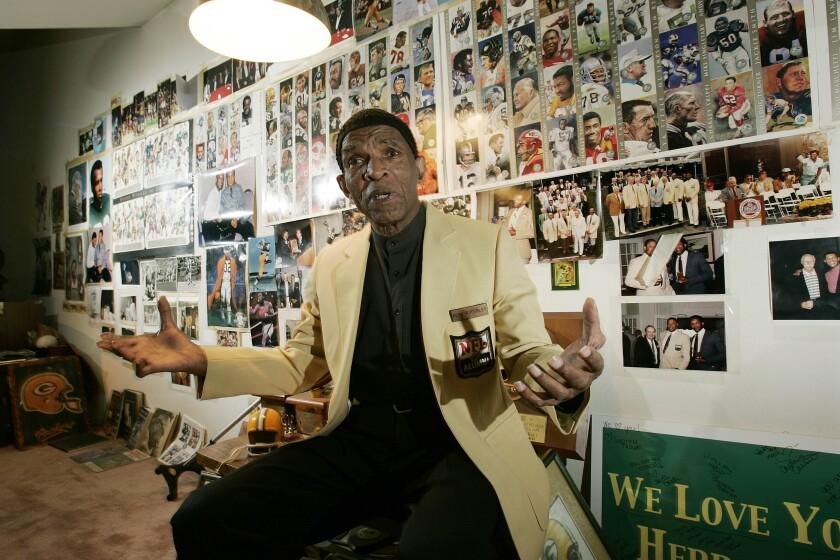 Hall of Fame cornerback Herb Adderley speaks as he sits in a room full of memorabilia.