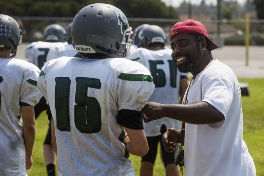 Brethren Christian's head coach Leon Green jokes with Slater Jones during practice in Huntington Bea