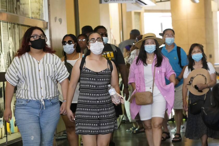 Visitors wear masks as they walk in a shopping district Thursday, July 1, 2021, in the Hollywood section of Los Angeles. (AP Photo/Marcio Jose Sanchez)