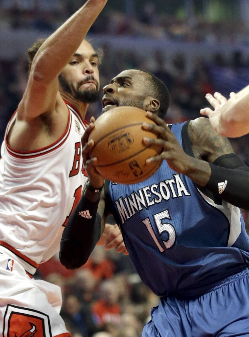 Minnesota Timberwolves forward Shabazz Muhammad, right, drives to the basket as Chicago Bulls center/forward Joakim Noah guards during the first half of an NBA basketball game on Saturday, Nov. 7, 2015,  in Chicago. (AP Photo/Nam Y. Huh)