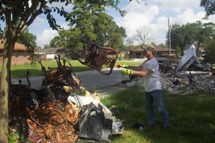 Fotografía que muestra a un hispano no identificado mientras realiza labores de limpieza en las afueras de su casa en Houston, Texas. EFE/Archivo
