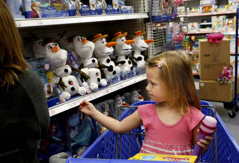 """A girl riding in a shopping cart reaches toward a shelf full of Olaf dolls from """"Frozen."""""""