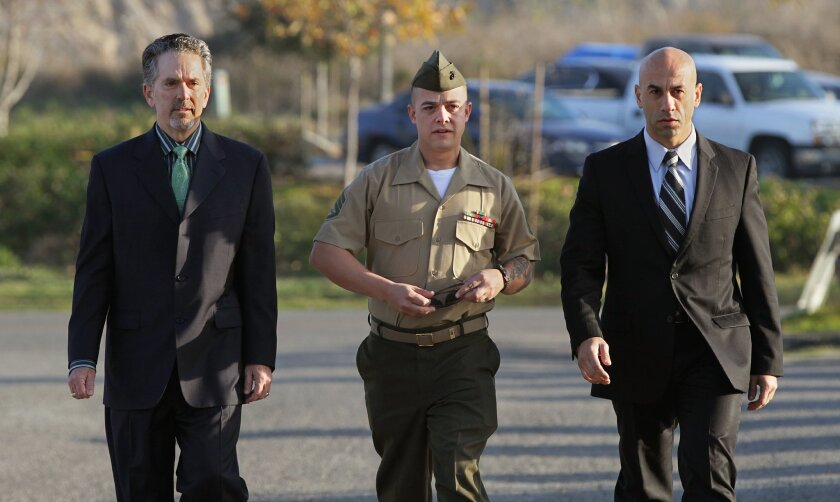 Marine Corps Staff Sgt. Frank Wuterich walks to the military courtroom Friday morning with his lawyers Neal Puckett, left, and Haytham Faraj, right.