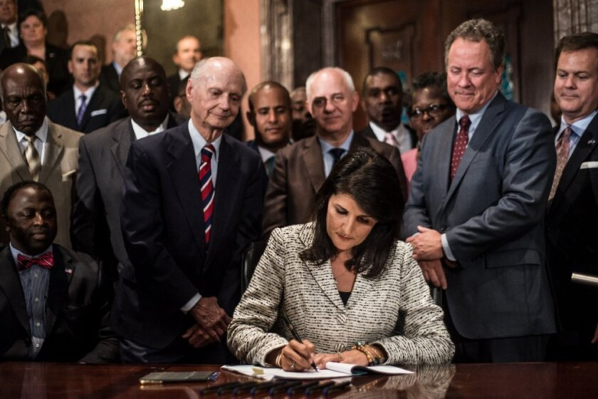 South Carolina Gov. Nikki Haley signs a bill to remove the Confederate battle flag from the state house grounds July 9, 2015 in Columbia, South Carolina. Debate on the flag was reignited three weeks ago after the mass murder at Emanuel AME Church in Charleston, South Carolina.