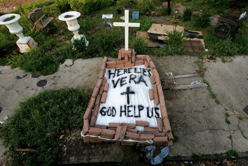 """FILE - In this Sept. 4, 2005, file photo, a makeshift tomb at a New Orleans street corner conceals a body that had been lying on the sidewalk for days in the wake of Hurricane Katrina. The message reads, """"Here lies Vera. God help us."""" Smith's cremated remains were later reburied in Texas, yet she remains part of her old community. (AP Photo/Dave Martin, File)"""