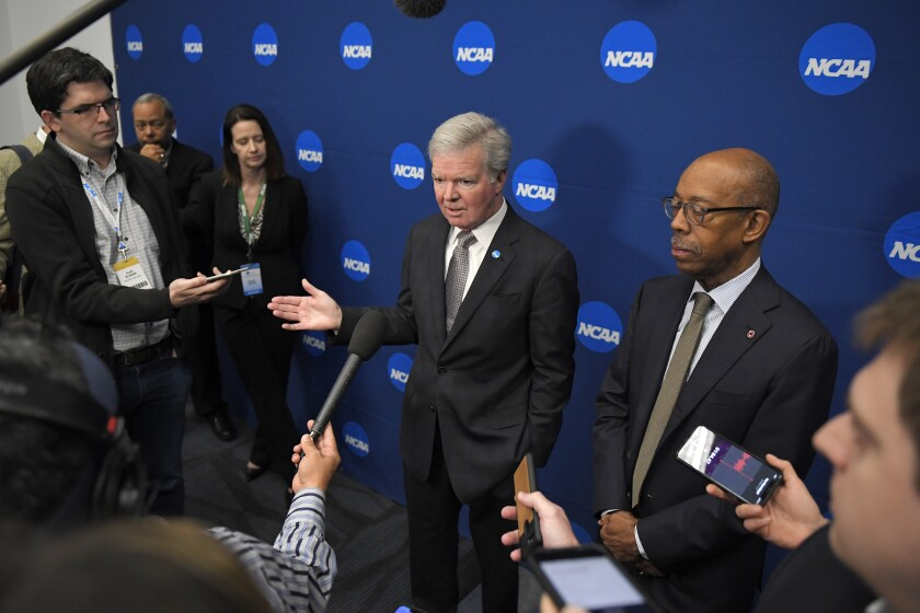 NCAA President Mark Emmert, center, speaks to reporters at the NCAA convention on Thursday in Anaheim.