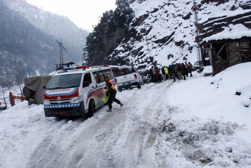 An ambulance heading to an area hit by avalanches, waits for a blocked road to be opened, in Keran, a small town in Neelum Valley, Pakistan-administered Kashmir, Tuesday, Jan. 14, 2020. Severe winter weather has claimed more lives as avalanches triggered by heavy snowfall killed more than 50 people in Pakistan-administered Kashmir while a dozen died in neighboring Afghanistan, officials said Tuesday. (AP Photo/M.D. Mughal)