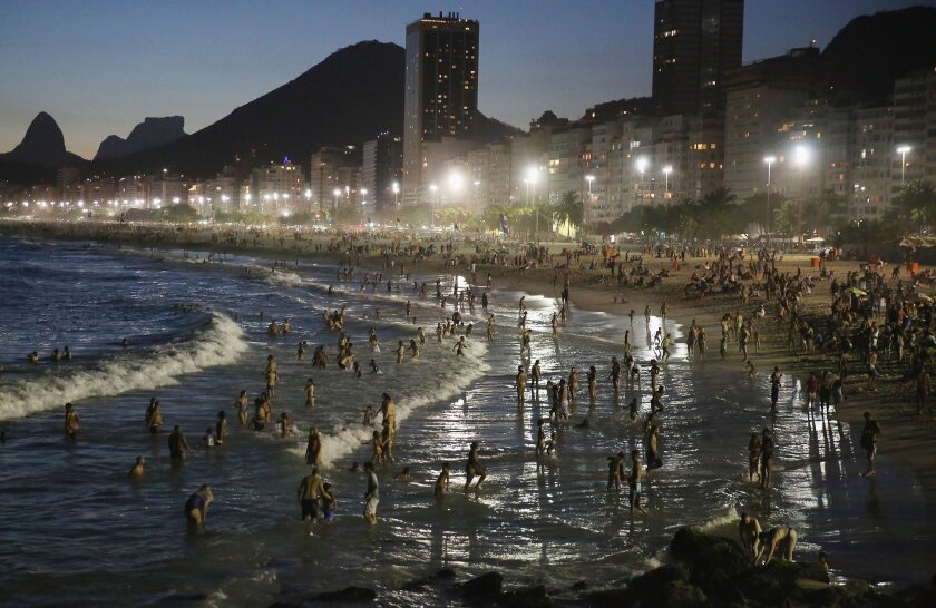 A summer heat wave sent residents of Rio de Janeiro to Copacabana beach as the sun set on Jan. 17. A new study says the planet's urban areas have been experiencing more heat waves and hotter nights over the past four decades.