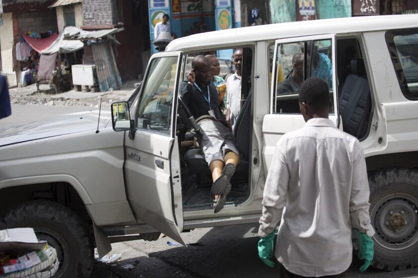 El cuerpo de la monja española Isabelle Sola Matas, yace en su auto en el centro de Puerto Príncipe, Haití. El juez local Noel Jean Brunet, dijo que dos hombres a bordo de una motocilcleta mataron a balazos a la monja católica romana de 51 años de edad mientras conducía. (AP Foto/Dieu Nalio Chery)