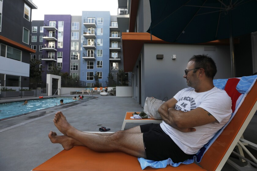 Mike Kaesermann, 38, relaxes as he watches his family play in the pool at an apartment building on Sixth Street, where they are renting a unit during their vacation.