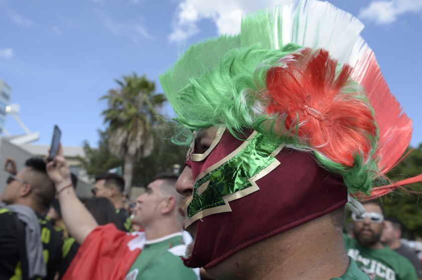 Saul Hernandez, right, of Sarasota, Fla., watches the Mexico team arrive by bus at the Orlando Citrus Bowl before a friendly soccer match against Costa Rica in Orlando, Fla., Saturday, June 27, 2015. (AP Photo/Phelan M. Ebenhack)