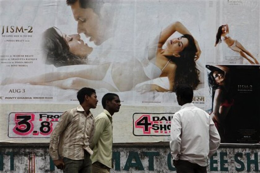"An Indian man watches a poster of Bollywood film ""Jism 2""  displayed outside a cinema in Hyderabad, India, Thursday, Aug. 2, 2012.  ""Jism 2"" stars a hard-core porn actress, and it does have that pesky title. But it's not a porn movie. Bollywood is certainly not ready for that. The film, which will"