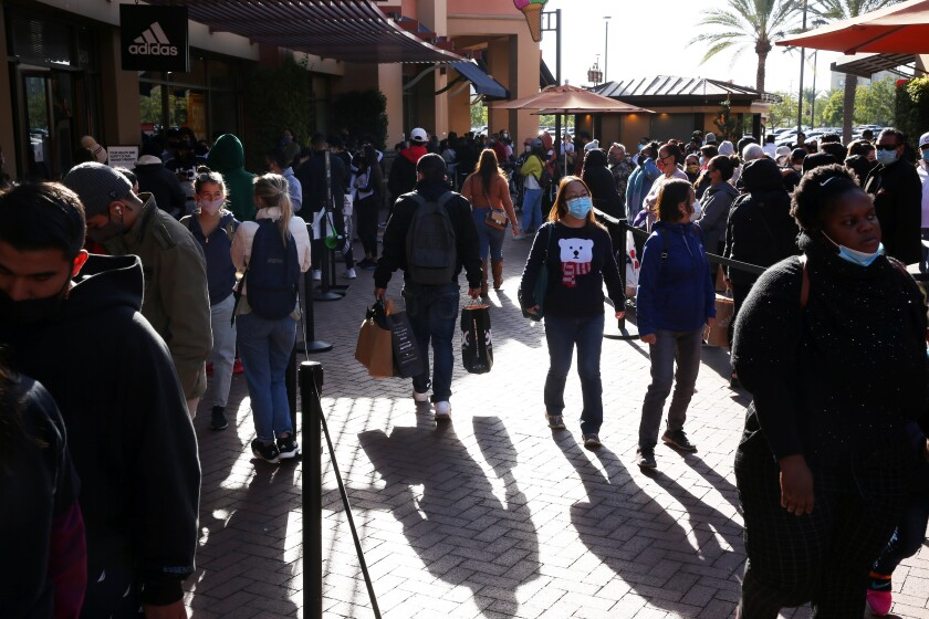 A large crowd of people at an outdoor shopping mall