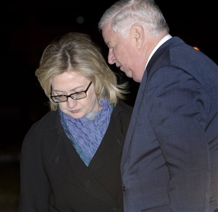 U.S. Secretary of State Hillary Rodham Clinton, left, is greeted by U.S. Ambassador Louis Susman as she arrives at Stanstead Airport in Essex, England, Monday, March 28, 2011. Clinton will be attending a conference on Libya on Tuesday. (AP Photo/Susan Walsh, Pool)