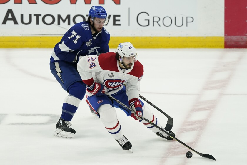 Montreal Canadiens left wing Phillip Danault (24) controls the puck next to Tampa Bay Lightning center Anthony Cirelli (71) during the second period in Game 2 of the NHL hockey Stanley Cup finals, Wednesday, June 30, 2021, in Tampa, Fla. (AP Photo/Gerry Broome)
