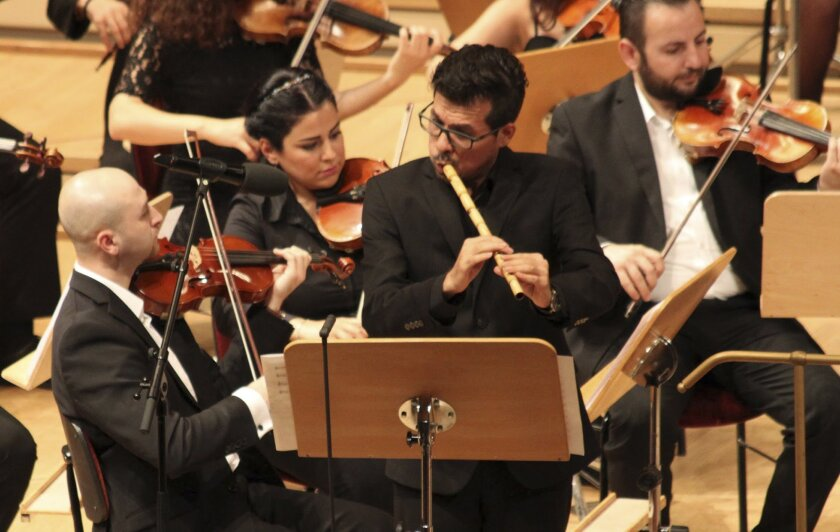 In this Sept. 11, 2016 photo Mohamad Fityan plays the Ney, a traditional Arabic flute, during a concert the Syrian Expat Philharmonic Orchestra in the Concert House in Berlin's Gendarmenmarkt. The Orchestra consists entirely of professional musicians who fled civil war in their homeland to seek ref