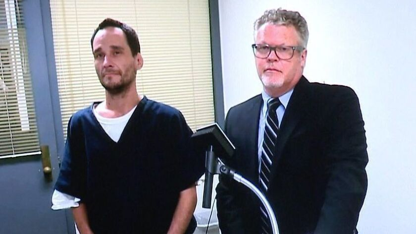 In a screen grab from a video arraignment, Matthew D. Barker (left) pleaded not guilty to assault wi