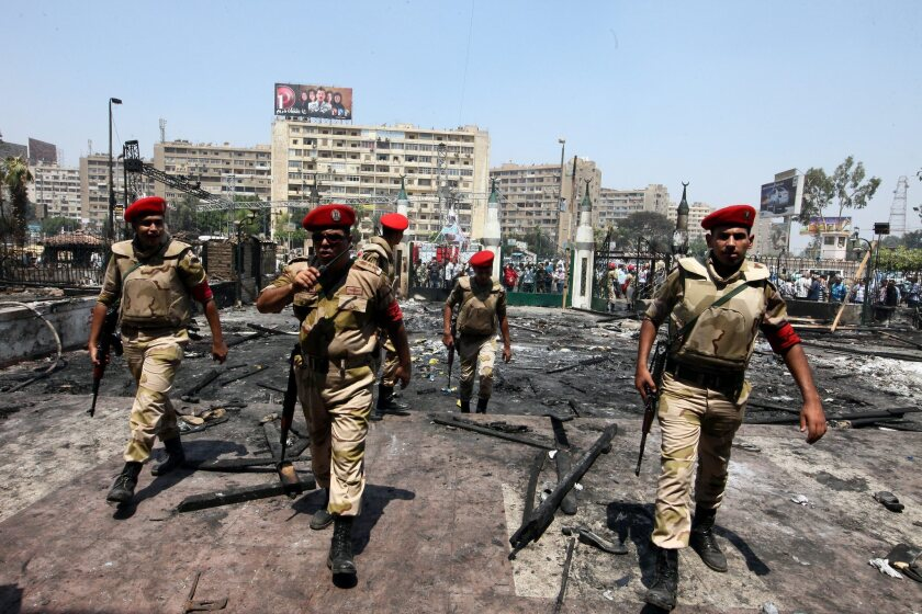 Egyptian soldiers stand guard in front of the burnt Rabaa Adawiya mosque on Aug. 15, 2013, the morning after the violent clearing of a sit-in around the mosque, in Cairo, Egypt. Egypt was cited by the U.S. State Department for human rights abuses in a report issued Thursday.