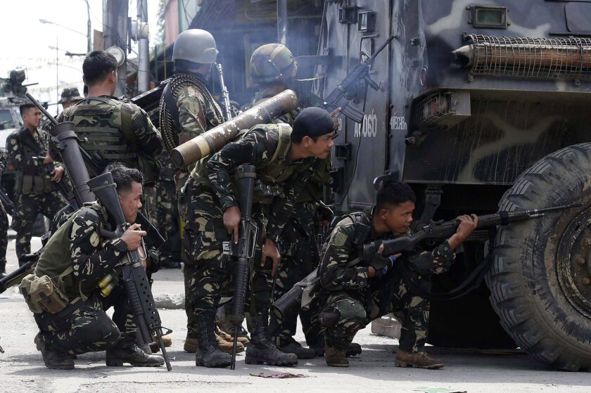 Philippine soldiers take up positions behind an armored personnel carrier during clashes in Zamboanga, in the southern Philippines. Nine people have died and thousands have been displaced by a three-day standoff with Muslim rebels holding about 200 hostages and using them as human shields.