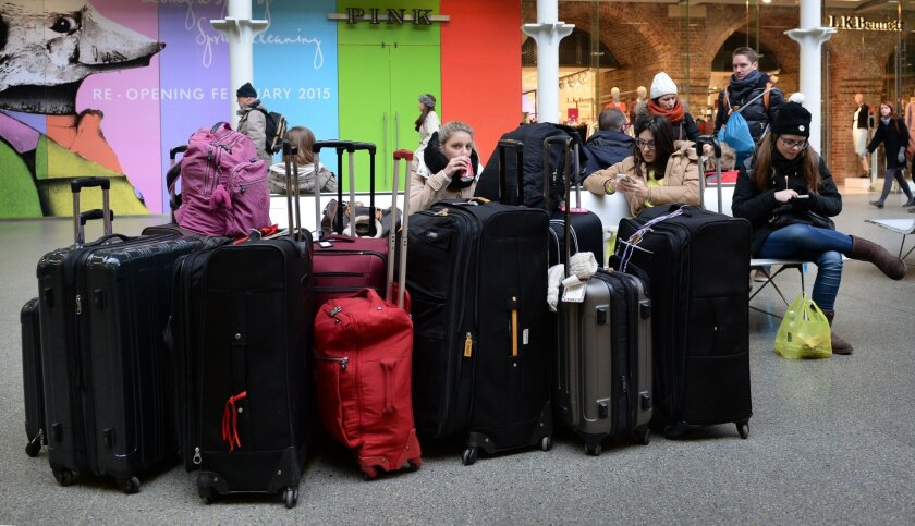 Commuters wait at St Pancras station in London, as Eurotunnel services have resumed but customers are told to expect delays,  Sunday, Jan. 18, 2015. Eurostar passenger services have resumed through the Channel Tunnel after a smoldering load on a truck triggered an alarm that shut down services and
