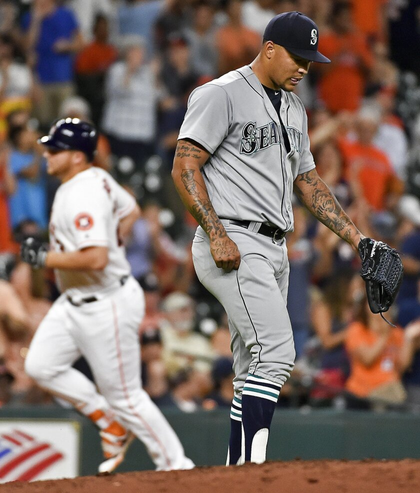 Seattle Mariners starting pitcher Taijuan Walker, right, looks away as Houston Astros' A.J. Reed, left, rounds the bases after hitting a two-run home run in the fourth inning of a baseball game, Tuesday, July 5, 2016, in Houston. (AP Photo/Eric Christian Smith)