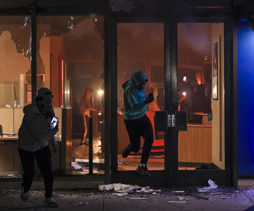 Looters break the glass door to gain access to Chase bank in La Mesa on Saturday before it burned down.