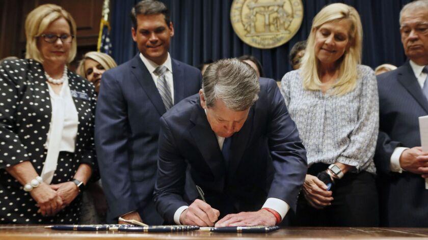 FILE - In this May 7, 2019, file photo, Georgia's Republican Gov. Brian Kemp, center, signs legislat