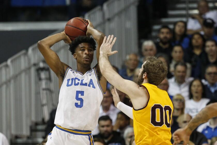 UCLA guard Chris Smith passes over Arizona State forward Mickey Mitchell.