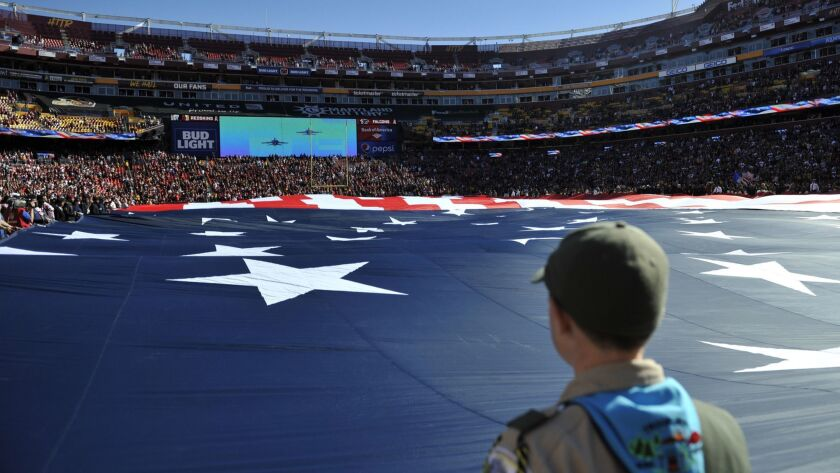 Boy Scouts lead the Pledge of Allegiance to begin a Veterans Day ceremony in Wrightwood, Calif., on