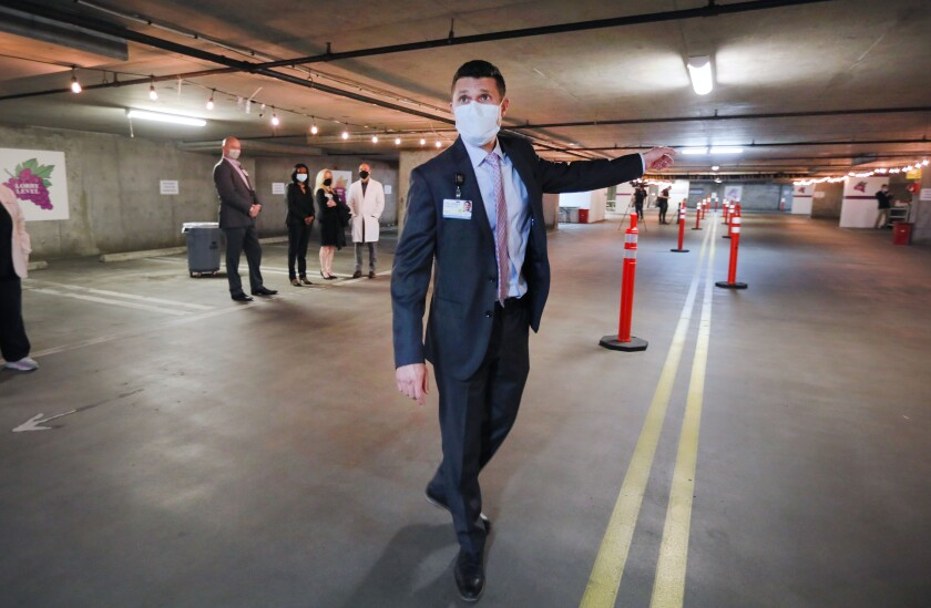 Brian Cohen of Palomar Health leads a tour of the COVID-19 vaccine station at the former Palomar Medical Center.