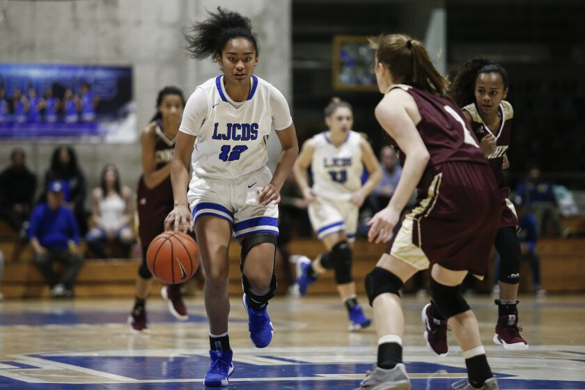 La Jolla Country Day point guard Te-hina Paopao (12) moves down the court under coverage from Bishop's guard Angie Robles (1) in the first period.