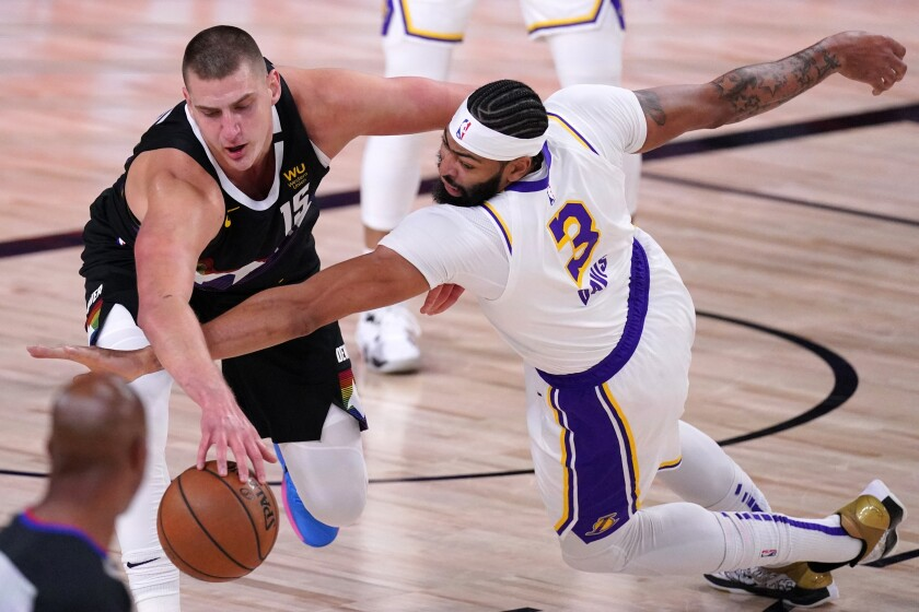 Denver Nuggets center Nikola Jokic, left, and Lakers forward Anthony Davis battle for a loose ball.