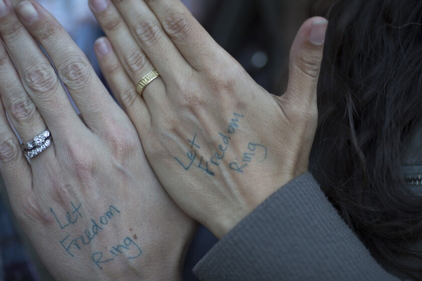 A couple show their wedding rings as they celebrate the Supreme Court ruling on same-sex marriage on June 26, 2015, in West Hollywood. Some say the ruling threatens religious freedom.