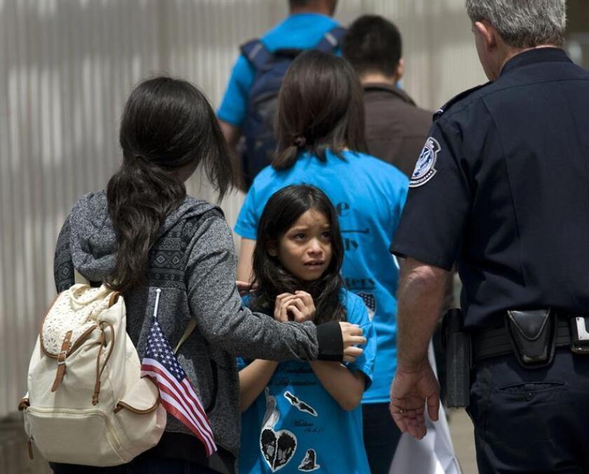 Mahalia Velazco (c), de 8 años, observa a un oficial estadounidense de fronteras mientras ingresa a Estados Unidos con su familia por la garita de San Ysidro en la frontera entre Estados Unidos y Tijuana, México. EFE/Archivo