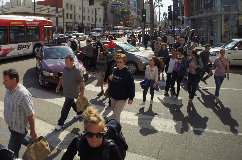 Pedestrians make their way around cars in the crosswalk at the intersection of Hollywood Boulevard and Highland Avenue in Hollywood.