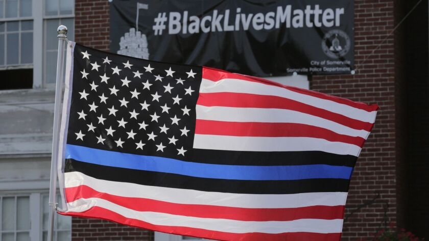 A flag with blue and black stripes in support of law enforcement officers flies at a protest by police and their supporters outside City Hall in Somerville, Mass., in 2016.