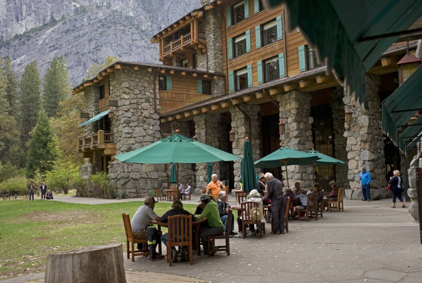 People dine outside the former Ahwahnee Hotel in Yosemite National Park.