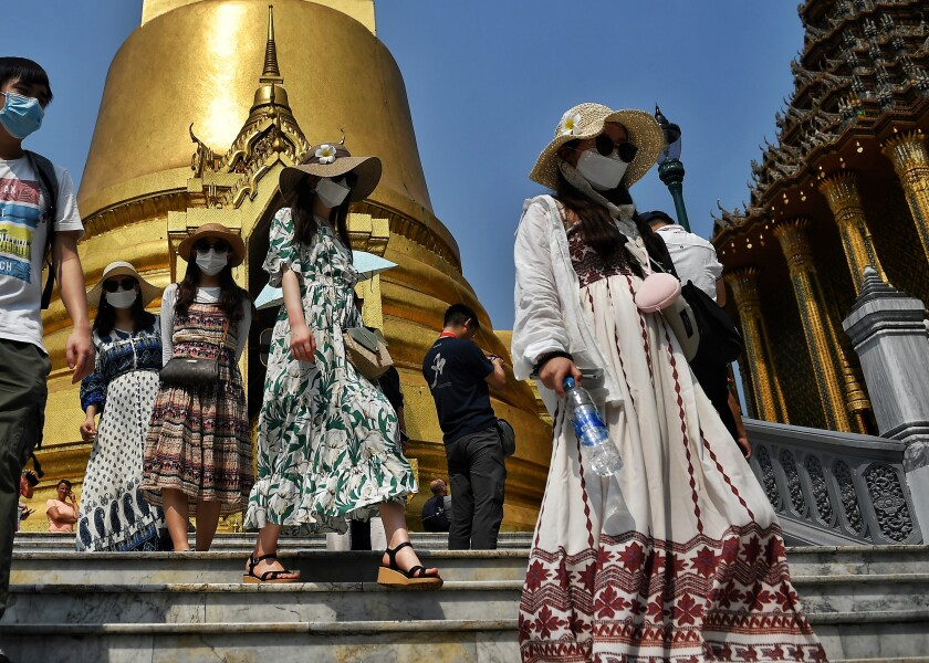 Tourists wearing face masks visit the Grand Palace in Bangkok on Jan. 29, 2020.