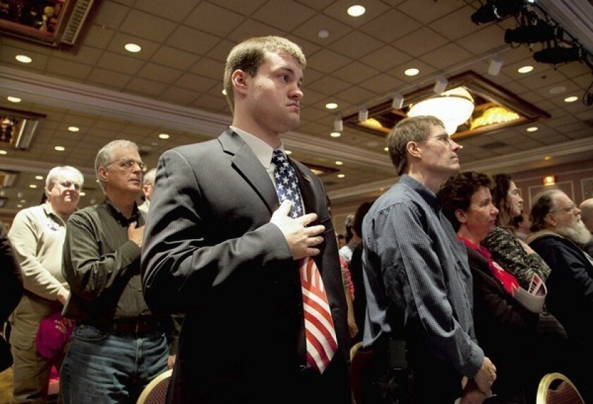 Members of the Wisconsin Faith and Freedom Coalition listen to the national anthem before a speech by Republican presidential candidate Mitt Romney.