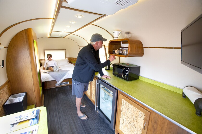 Two people check out the interior of a vintage trailer