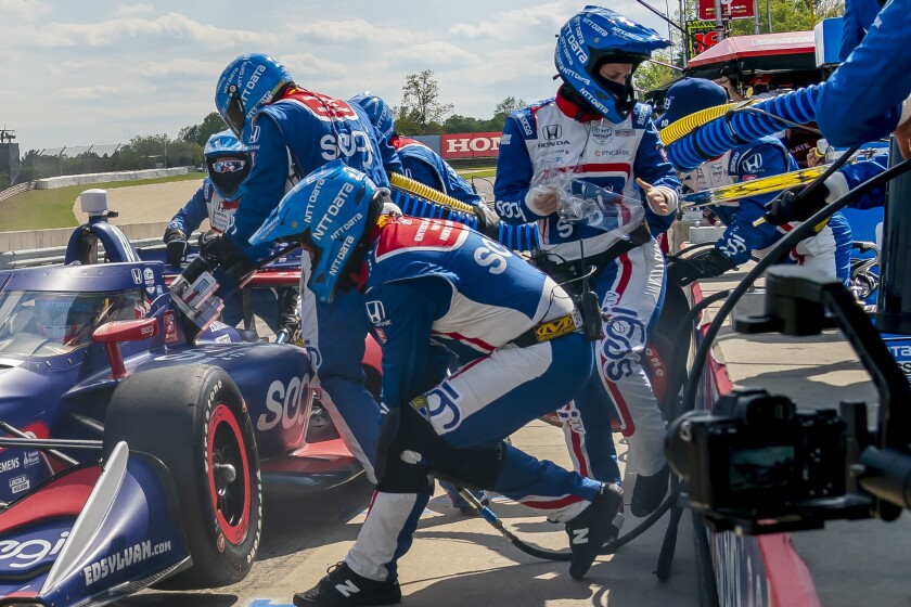 In this photo provided by Chip Ganassi Racing, Danielle Shepherd, at right with the clear sheet in her hand, works in the pit for auto racing driver Alex Palou during the Honda Indy Grand Prix of Alabama auto race at Barber Motorsports Park., Sunday, April 18, 2021, in Birmingham, Ala. Shepherd went over the wall when tasked with removing the tear off from the aeroscreen on Palou's car. The last three IndyCar races have been won by drivers who have female engineers on their teams, a trend that could continue Sunday at Mid-Ohio Sports Car Course. (Walter G. Arce/Chip Ganassi Racing via AP)