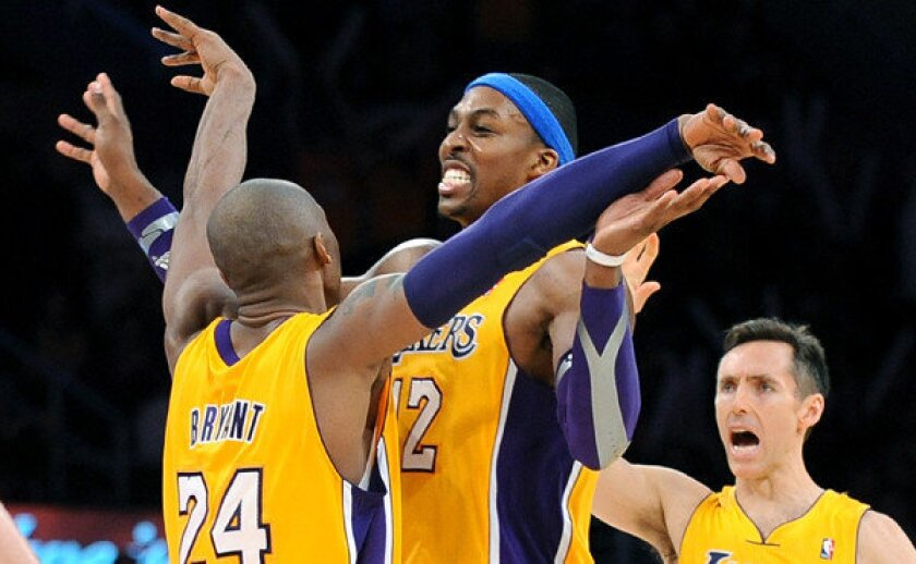Kobe Bryant, left, celebrates with the teammate Dwight Howard, center, as Steve Nash looks on during a game against the Utah Jazz.