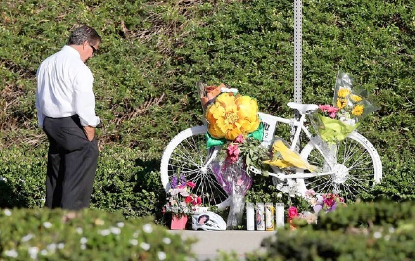 "A visitor pauses at the Ghost Bike-style memorial site on Newport Coast Drive on Monday for Dr. Catherine ""Kit"" Campion Ritz, who police say was killed by a hit-and-run driver Saturday. Campion Ritz, 57, of Irvine practiced at Newport Family Medicine."