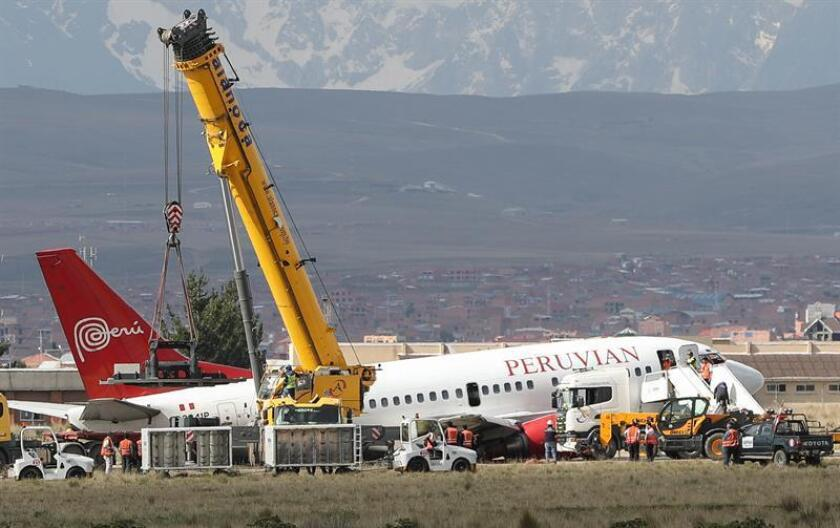 Workers of the El Alto International Airport try to tow a plane near El Alto, Bolivia, 22 November 2018. A Peruvian Airlines plane forced the temporary closure of the El Alto International Airport runway after the aircraft skidded and fell on one side during an incident during landing. EPA-EFE/MARTIN ALIPAZ