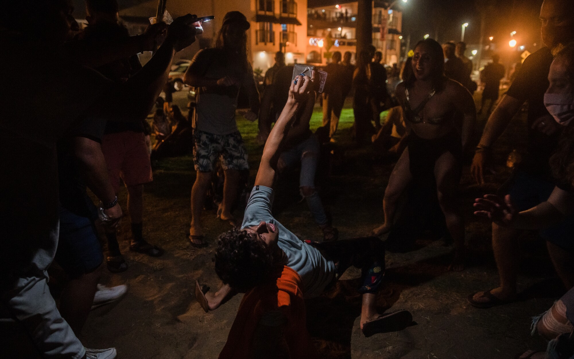 People with and without face masks dance in Ocean Beach on Wednesday night.